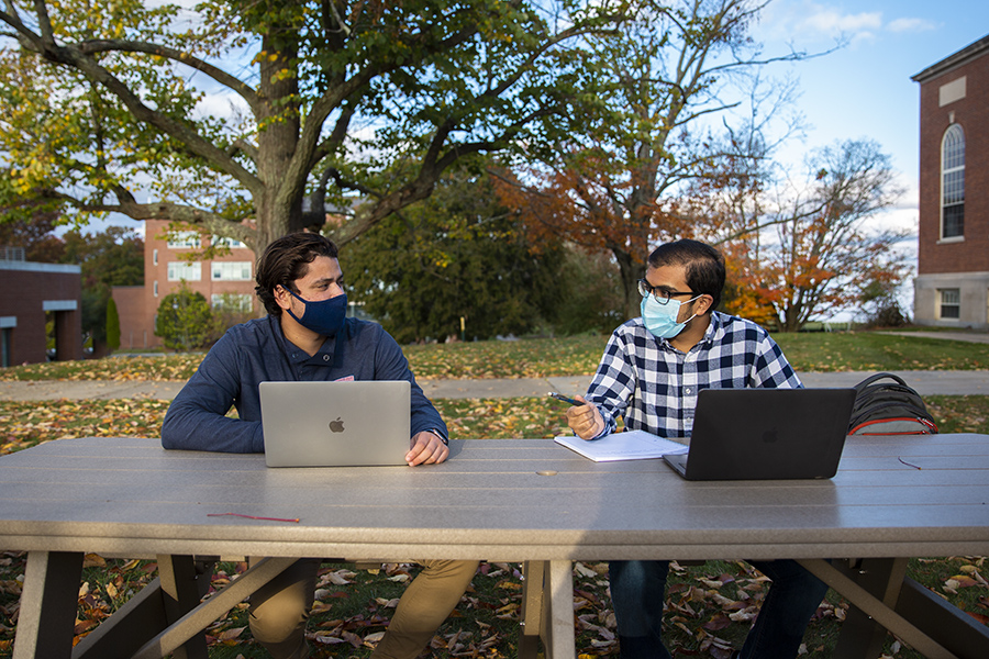 Two students wearing masks study outside on a fall day.