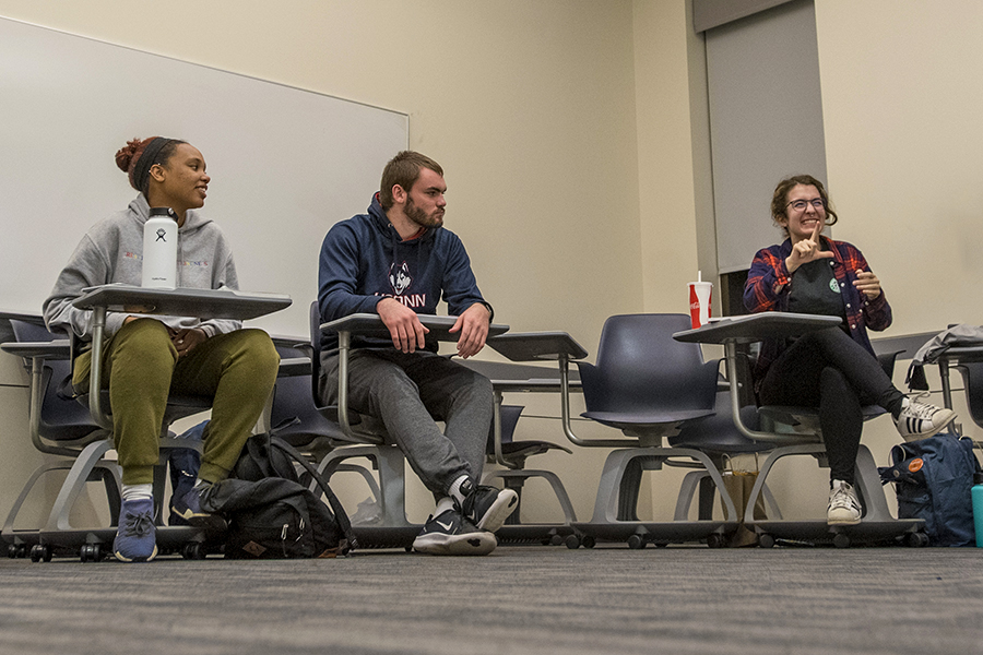 Three students signs during an American Sign Language class.